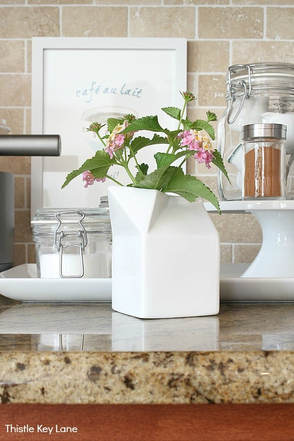 Flowers displayed in a creamer - Organizing A Coffee Station And A Free Printable