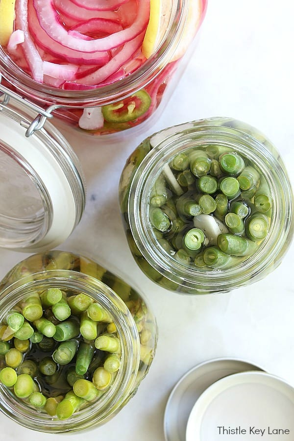 Recipe for Sweet Spicy Refrigerator Pickled Green Beans - top view of open jars with white background.