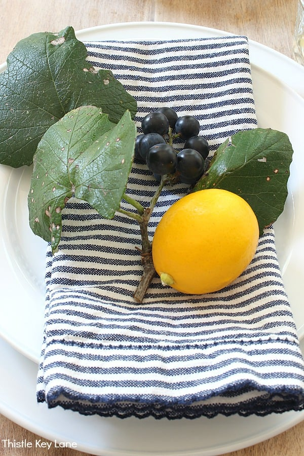 Black grapes and leaves with a lemon on navy and white napkin. Summer Lemon Tablescape And A Free Printable.