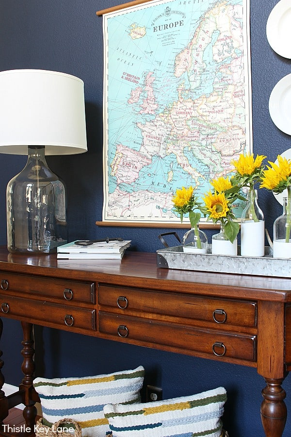 Table with navy wall large lamp, map and flower arrangement - Summer To Fall Entry Table With Sunflowers.