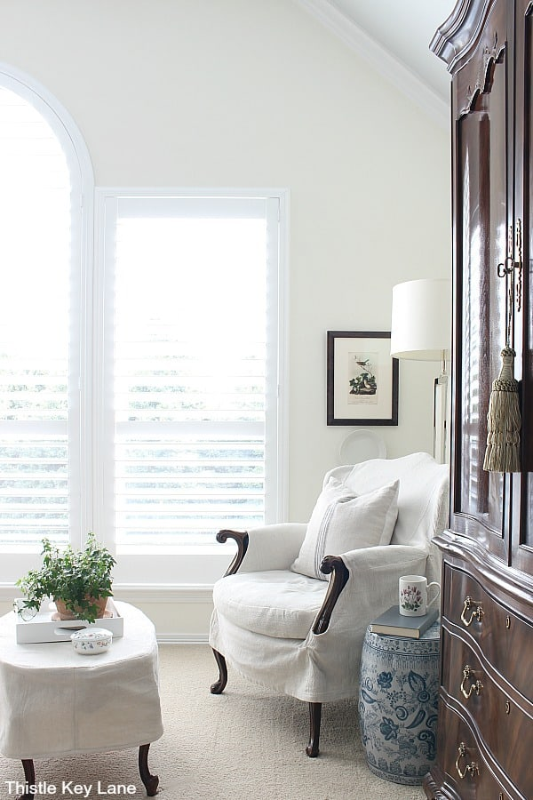 Bedroom sitting area with slipcovered chair, table and lamp. How To Create A Cozy Reading Nook.