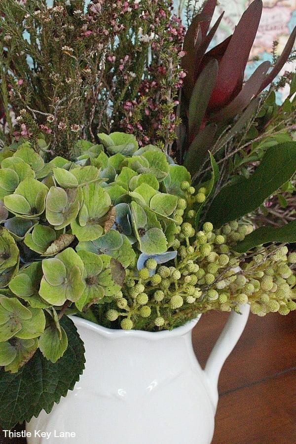 Up close hydrangea and greenery in ironstone pticher.