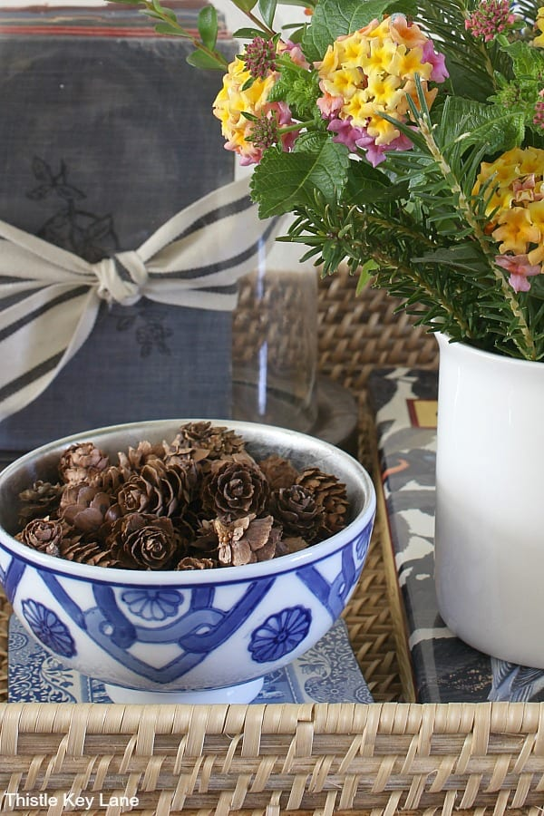 Blue and white bowl with mini pinecones on a wicker tray.