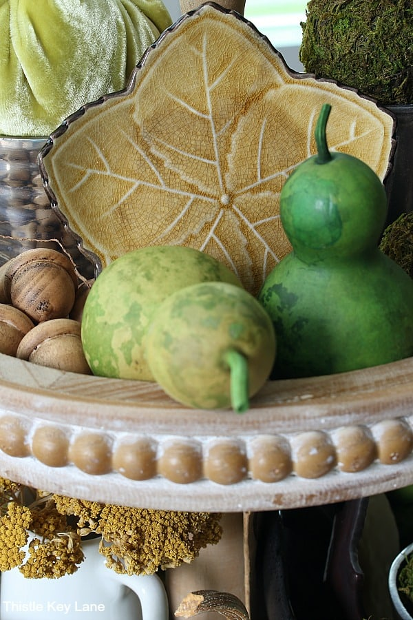 Green gourds and a yellow dish on a tiered tray.
