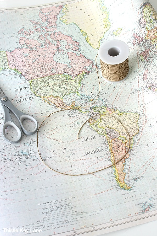 World map with scissors and waxed cotton string.
