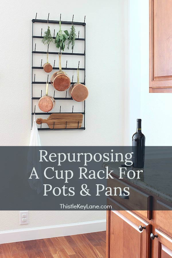 Wall rack with copper pots, herbs and a cutting board.