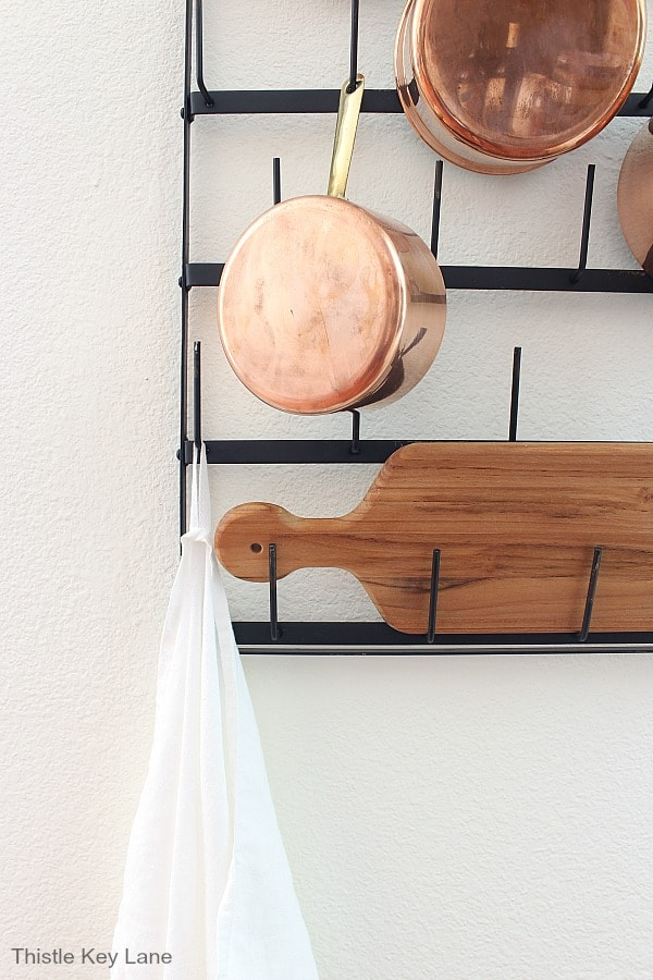 Pot rack with cutting board and linen kitchen towel.