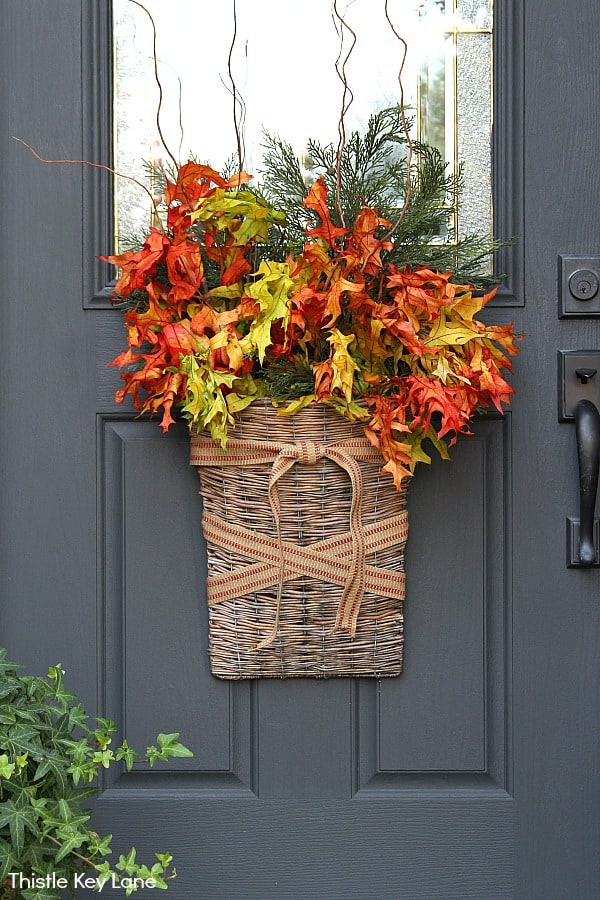 Full view of a door basket with fall colored leaves. Fall Decorating Ideas For A Small Porch.