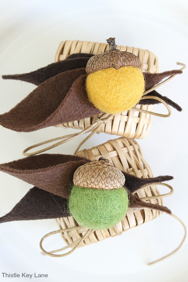 Green and yellow felt acorns on woven napkin rings. DIY Felt Acorn Napkin Rings.