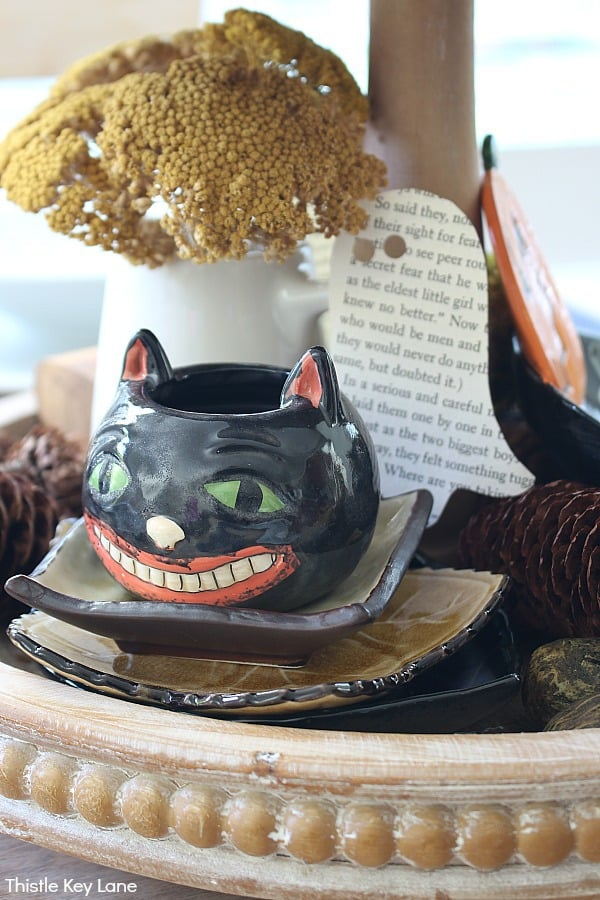 Black Cat Candle Holder Sitting On A Stack Of Dishes - Create A Last Minute Halloween Tiered Tray.