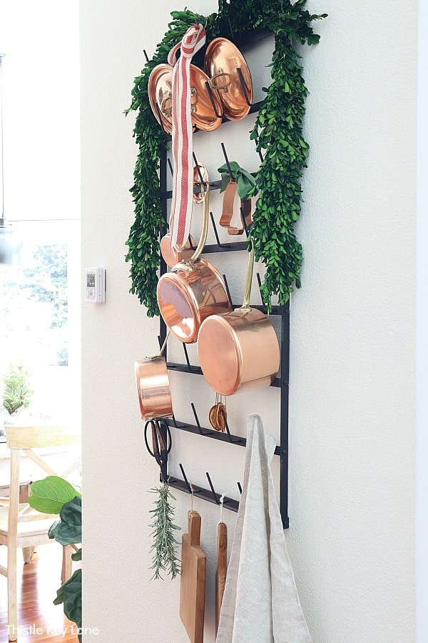Copper pots on a rack with boxwood garland. Christmas In The Kitchen And Family Room.
