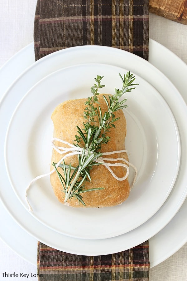 Mini bread loaf with rosemary and thyme tied with string. Thanksgiving Fruit And Flower Tablescape.