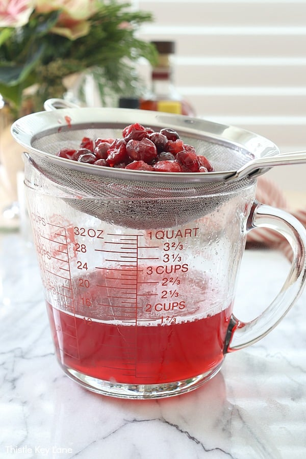 Large measuring cup with cranberries in a strainer.