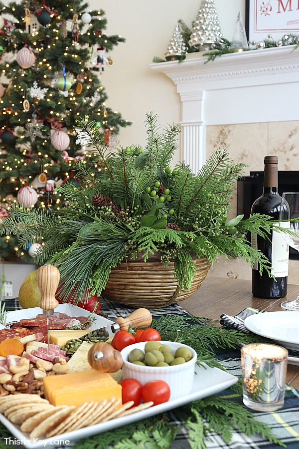 Evergreen centerpiece, plaid tablecloth and a charcuterie tray. Evergreen Christmas Centerpiece And Tablescape.