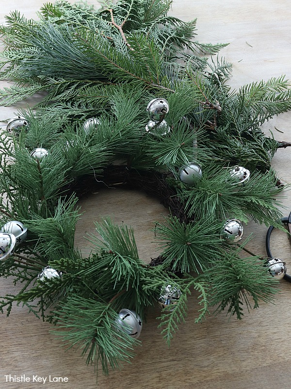 Pine wreath with silver jingle bells and a bundle of greenery.