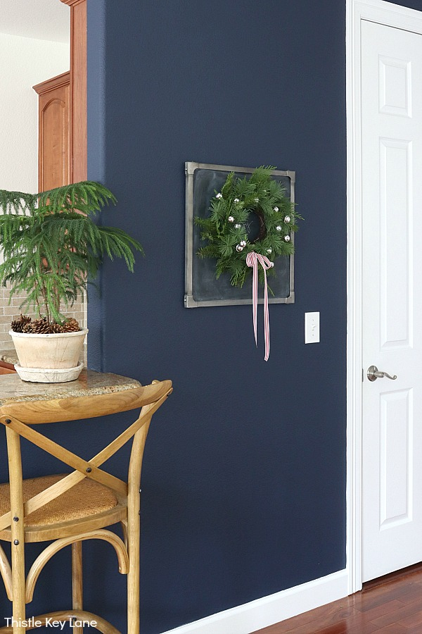 Wreath on a chalkboard on navy wall. How To Update A Wreath With Greenery.
