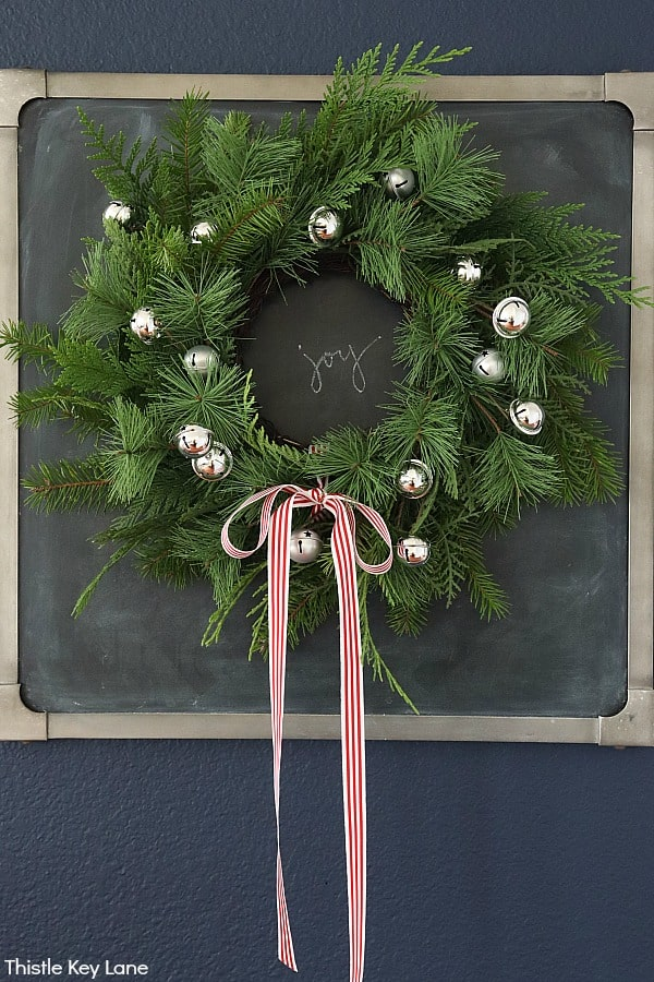 Pine wreath hanging on a chalkboard. How To Update A Wreath With Greenery.