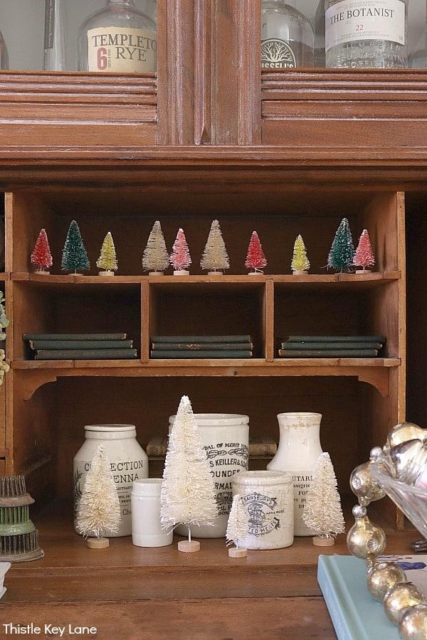 Bottle brush trees and ironstone jars on a secretary desk. White Bottle Brush Tree Vignette.
