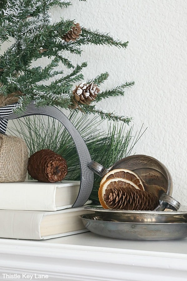 Vintage silver stacked with orange slices and pinecones. Transitioning From Holiday To Winter Decor - Use these simple winter decorating ideas to make your home feel warm and cozy after the holidays. Winter Decorating Ideas. Winter Decorating After Christmas. How To Make A Home Feel Cozy. Decorating With Faux Pine Trees. Decorating With Vintage Silver.