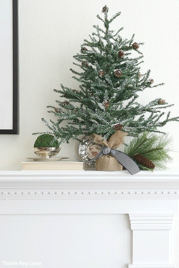 Snowy pine tree on mantel with ticking bow. Transitioning From Holiday To Winter Decor - Use these simple winter decorating ideas to make your home feel warm and cozy after the holidays. Winter Decorating Ideas. Winter Decorating After Christmas. How To Make A Home Feel Cozy. Decorating With Faux Pine Trees. Decorating With Vintage Silver.