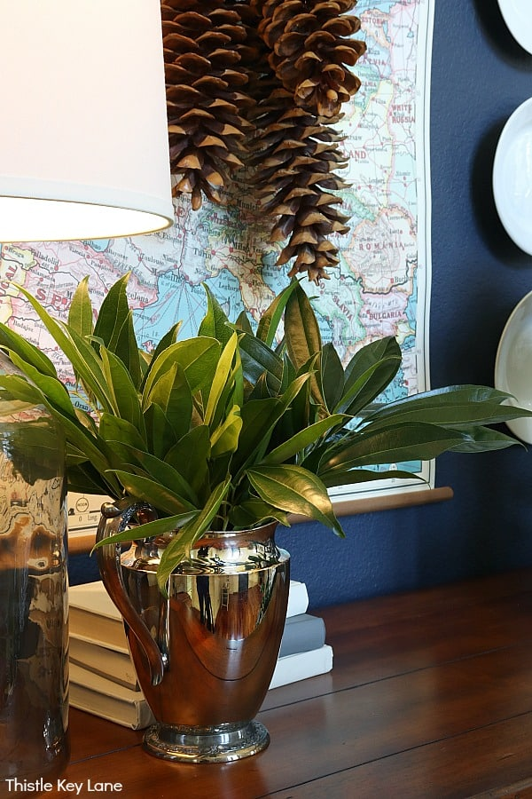 Greenery in a silver pitcher and a map on the wall. Winter Entry Table And A Pinecone Swag.