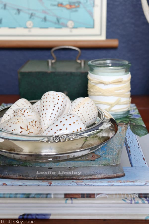 Sea shells in a glass and silver bowl and a candle holder. Early Spring Entry Table.
