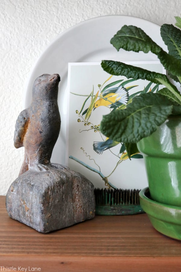 Styling floating shelves with a prim rose, Audubon print and a rustic bird figure.