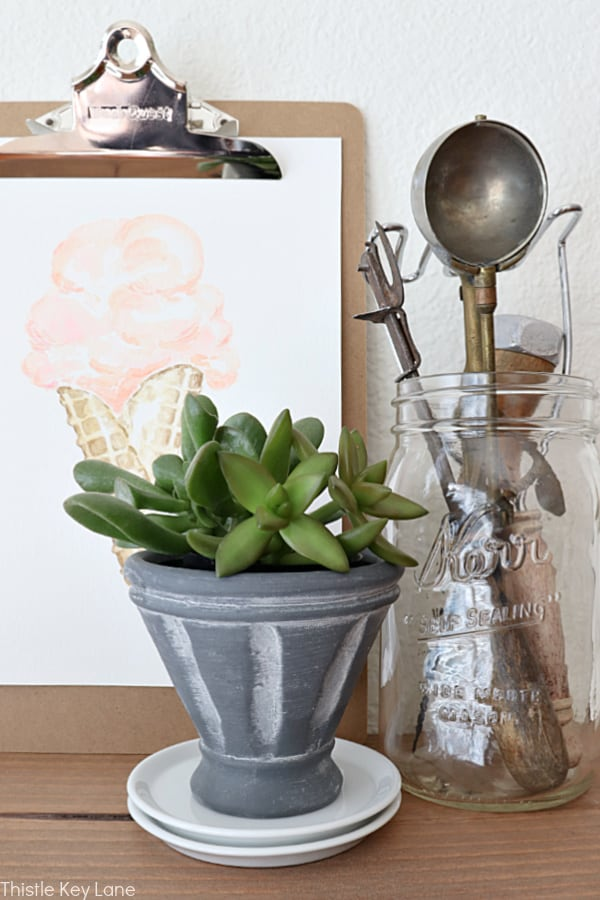 Easy Ways To Style Floating Shelves - Succulent in gray French bowl.