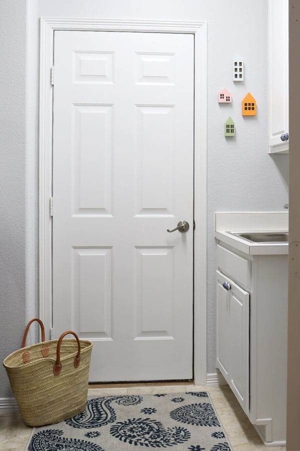 Pass through laundry room with colorful art on the wall. Laundry Room Organizing Ideas.