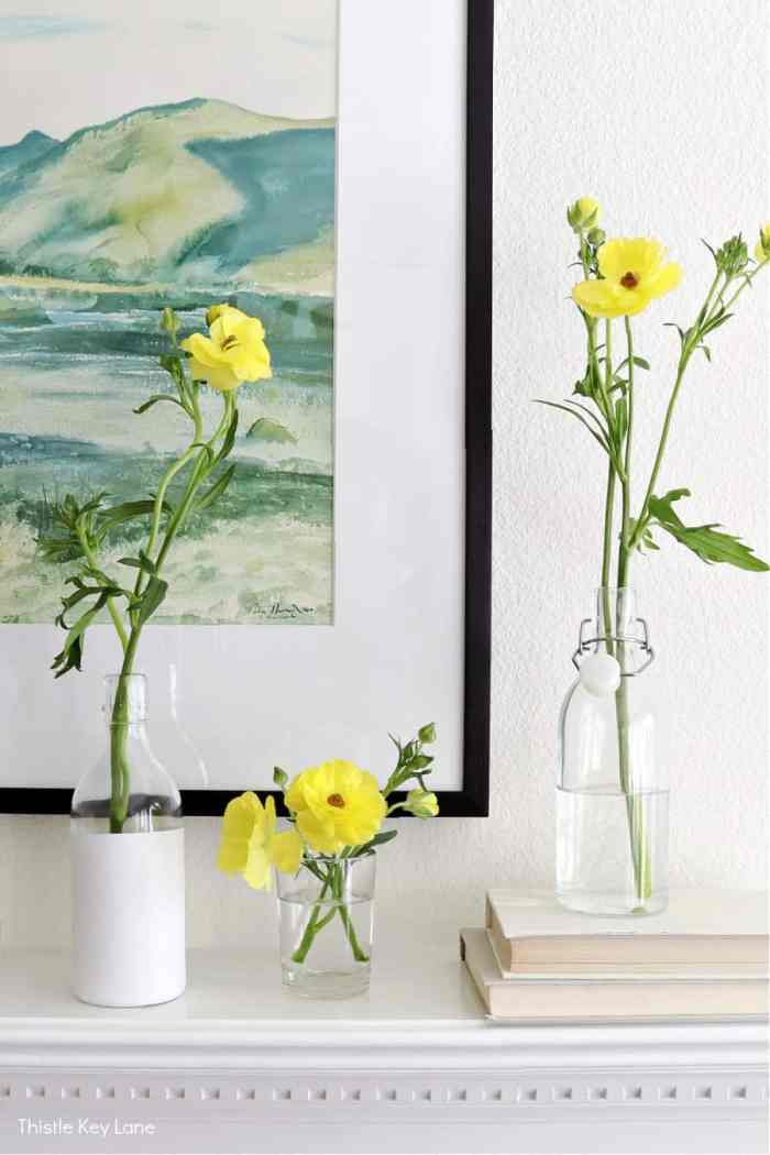 Clear glass and painted bottles holding yellow flowers. Spring Mantel With Flowers And Bottle Vases.