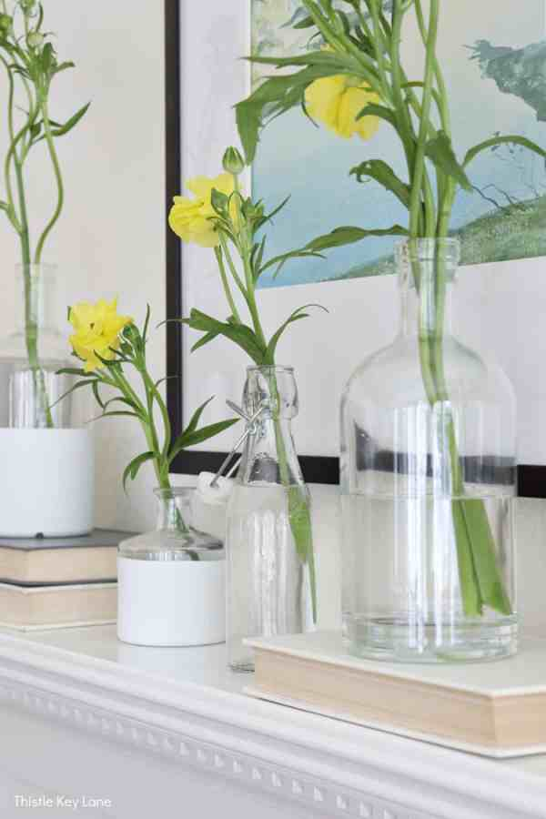 Fresh flowers in bottles on a white mantel. Spring Mantel With Flowers And Bottle Vases.
