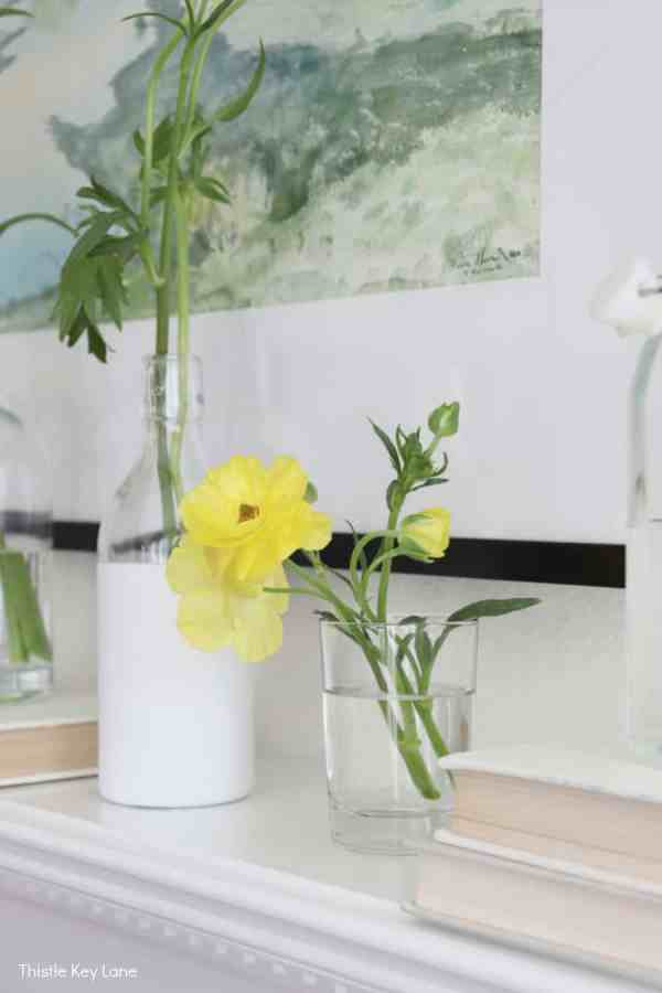 Yellow ranunculus in a glass on the mantel.
