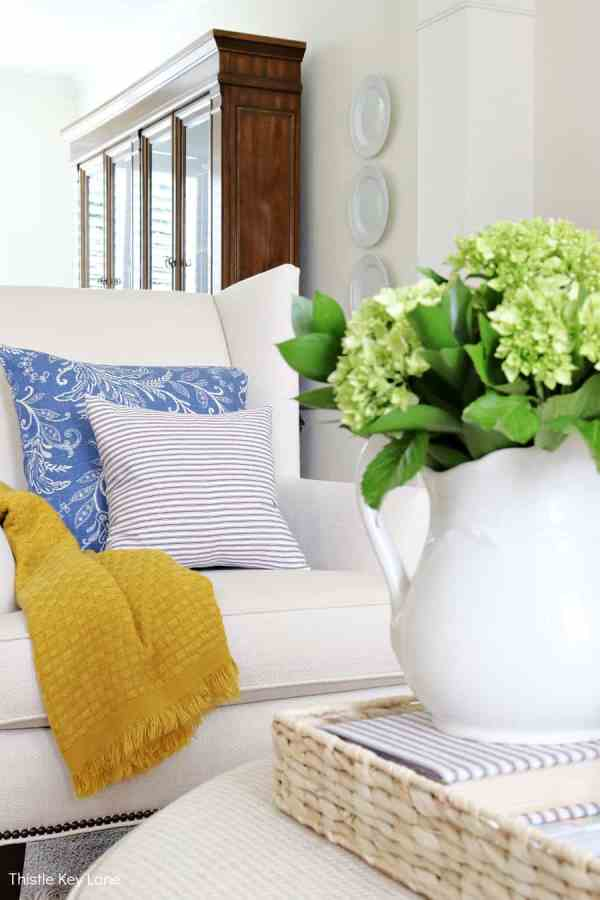 White vase with greenery on a tray. Decorating With Hints Of Blue.
