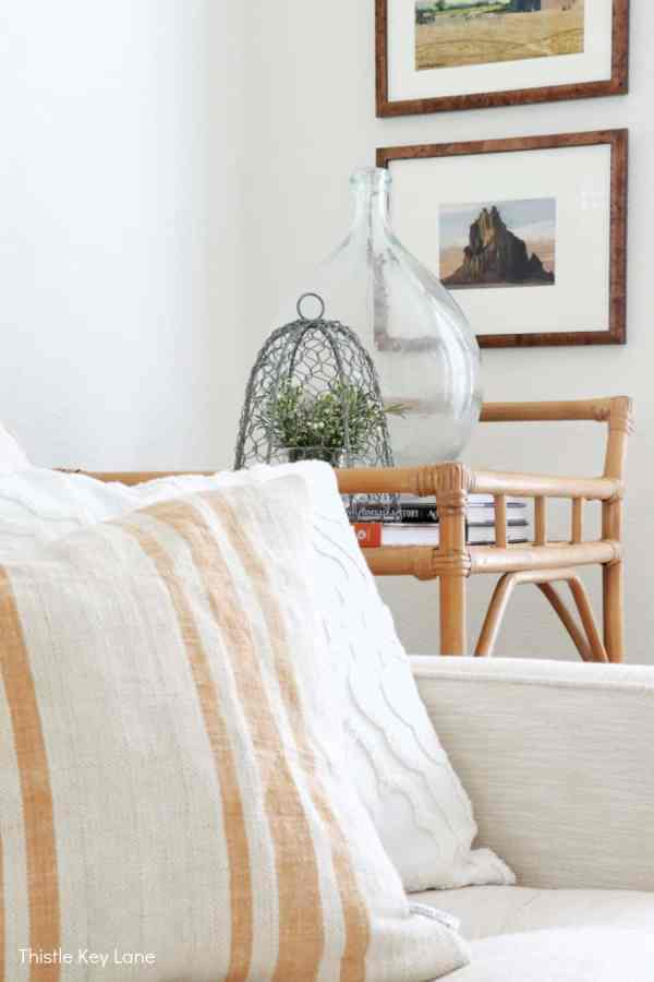 Grain sack pillows, neutral furniture, bar cart with glass demijohn and landscape watercolors.