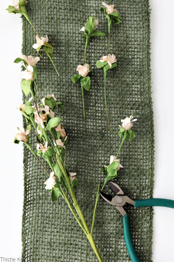 Flower pick with light pink paper blooms. Spring Burlap And Carrot Wreath.