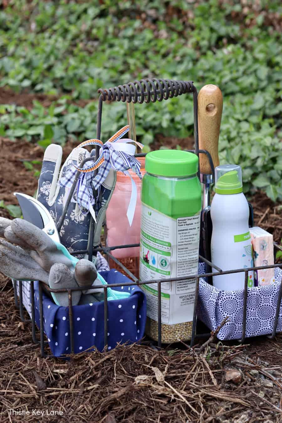 Garden caddy with supplies sitting on bark mulch. DIY Garden Tool Caddy.
