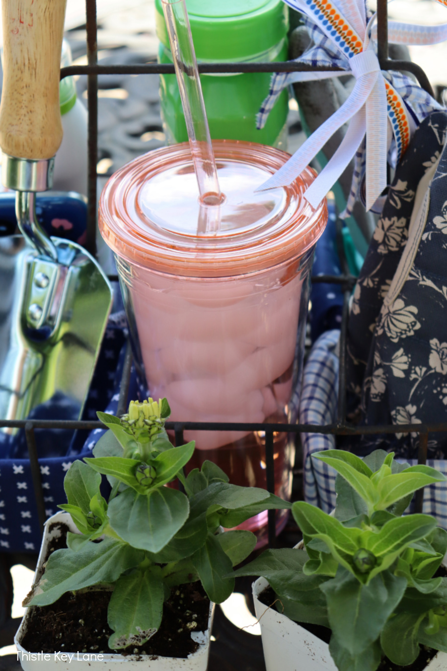 Peach drink tumbler on DIY garden tool caddy.