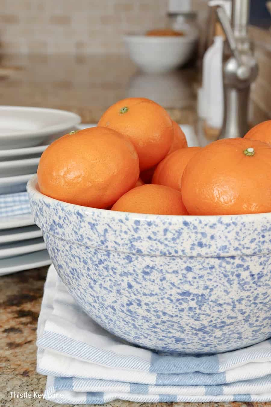 Blue and white speckled bowl holding oranges - Using Trays To Control Kitchen Clutter.