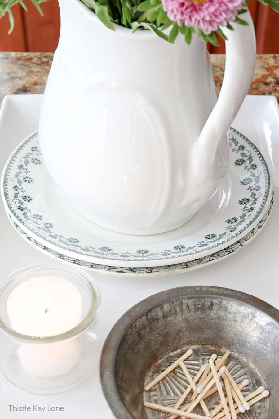 Blue and white plates, ironstone pitcher, candle, tin holding matches - Using Trays To Control Kitchen Clutter.