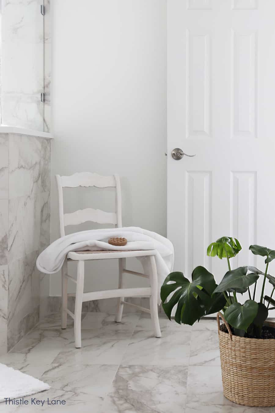 Vintage cane chair and monstera plant. White And Gray Bathroom Makeover.