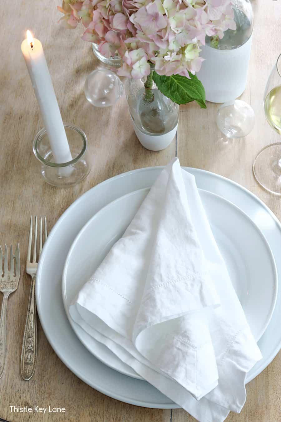 White linen napkins casually arranged on white plates.