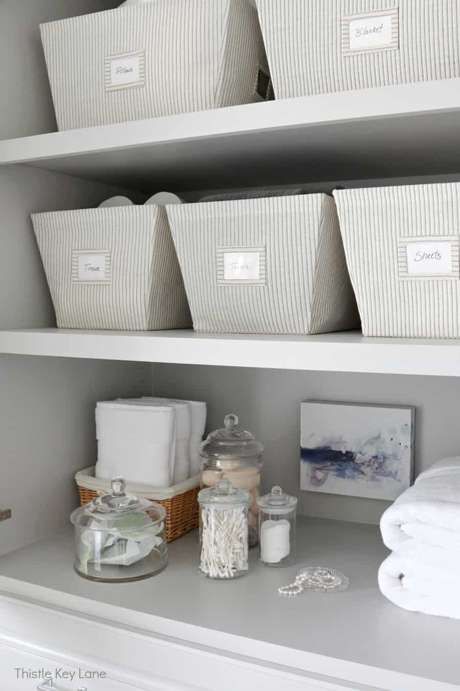 Canvas storage bins for towels and sheets. Organizing A Master Bathroom Linen Closet.