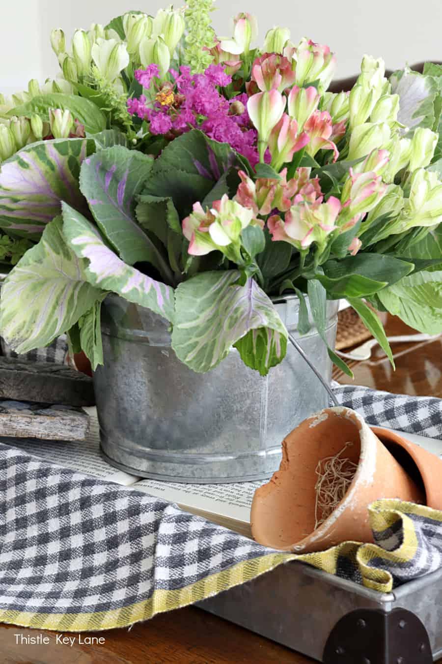 Fresh flowers, gingham fabric and terra cotta pots. Kale Flower Arrangement And Garden Tablescape.