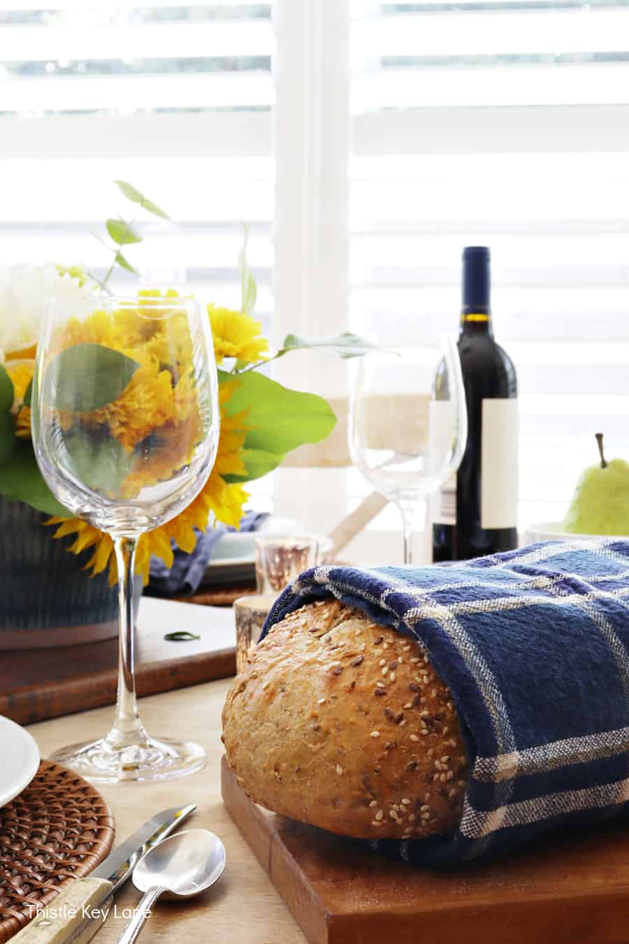 Bread wrapped in a navy plaid napkin on a bread board. Early Fall Tablescape With Sunflowers.