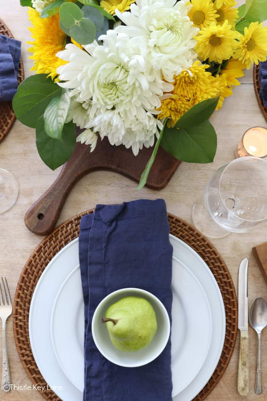 Rattan charges with white dishes and navy napkins.