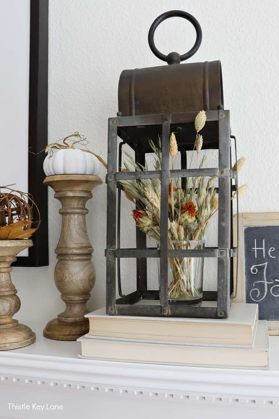 Vintage lantern with a flower arrangement inside. Decorating A Fall Mantel With Dried Arrangements.