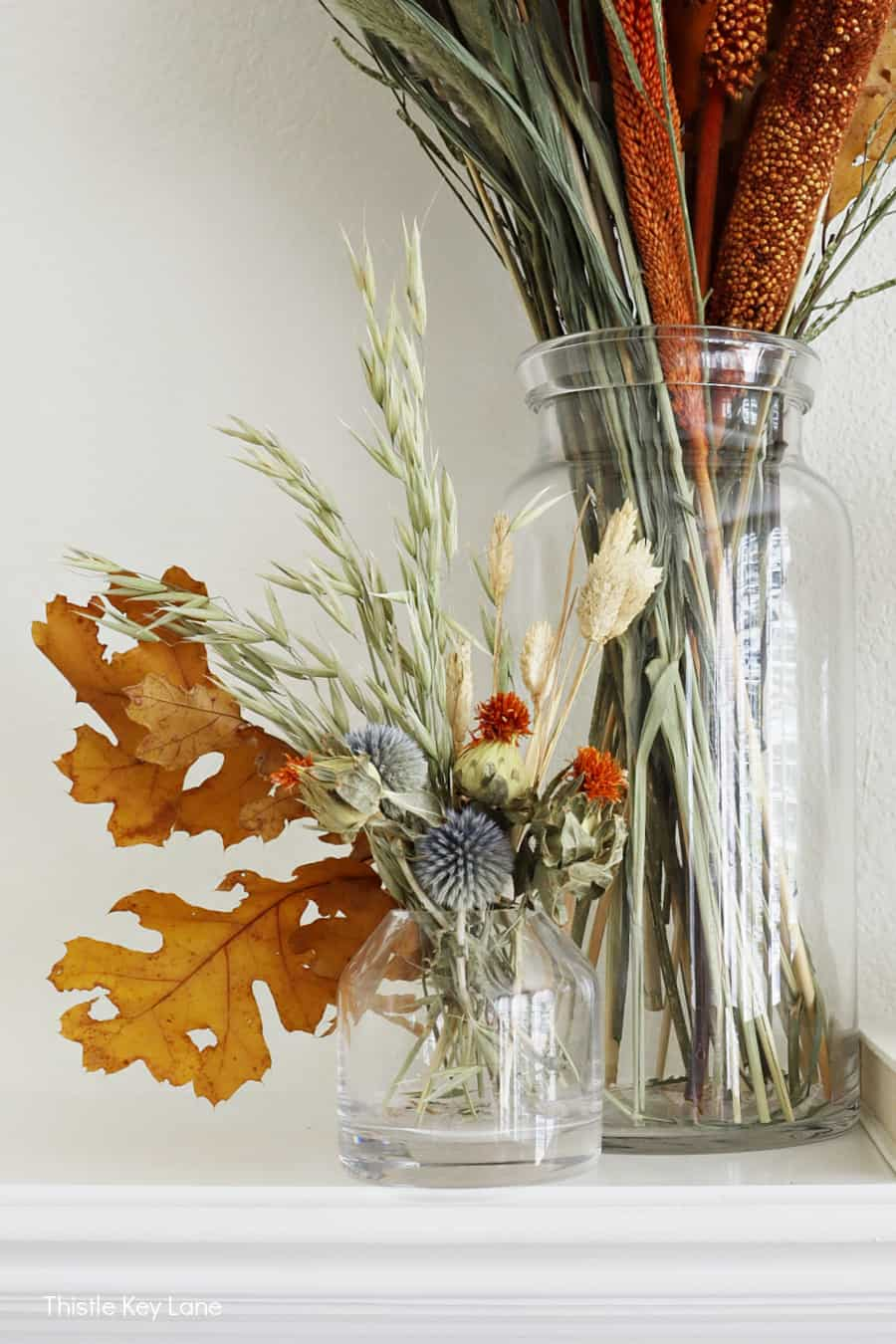 Fall leaves and grasses in a short glass vase.