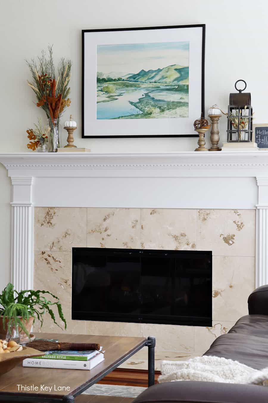 White mantel with watercolor print decorated with fall arrangements. Decorating A Fall Mantel With Dried Arrangements.