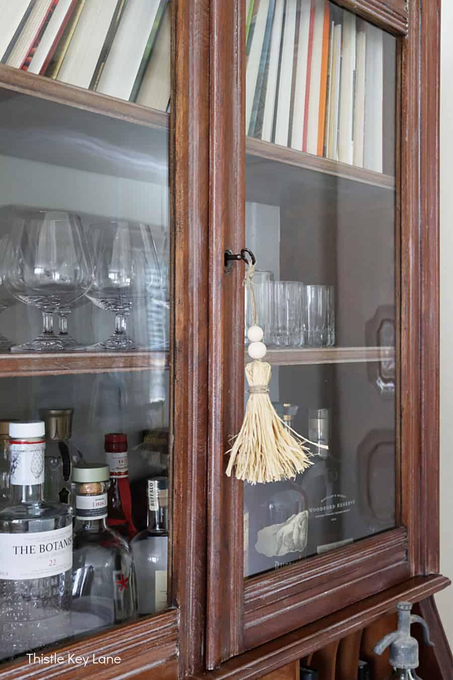 Raffia tassel handing from key in liquor cabinet. How To Make Raffia Tassels.