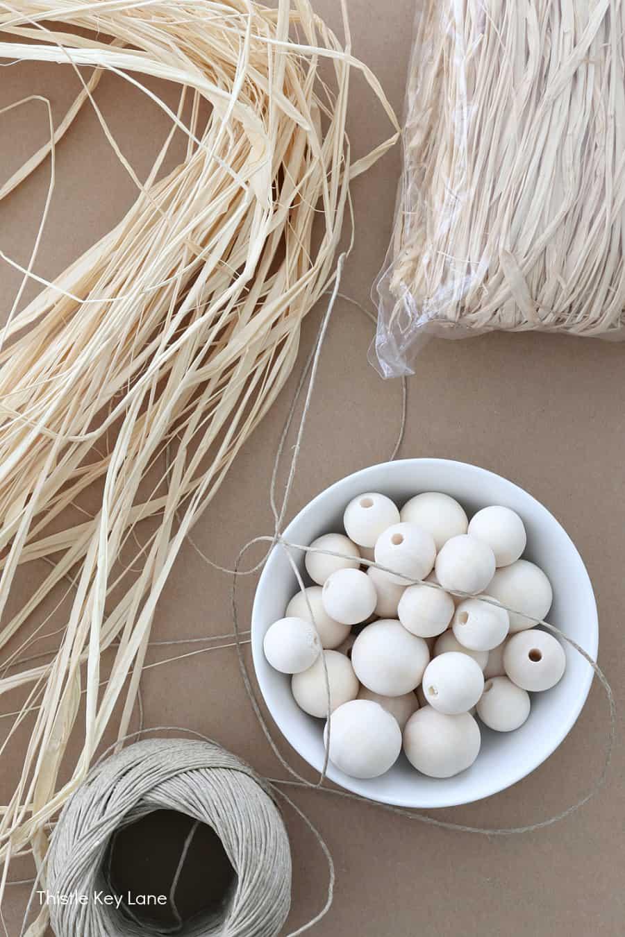 Raffia strands, beads in a bowl and a ball of hemp string. How To Make Raffia Tassels.